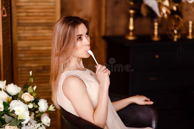 Une belle jeune femme dans une robe beige lèche une cuillère à l'intérieur figure idéal photos stock