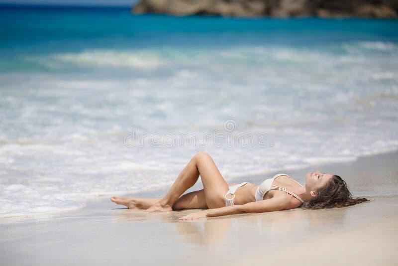 Une belle jeune femme dans un bikini avec la planche de surf photo stock