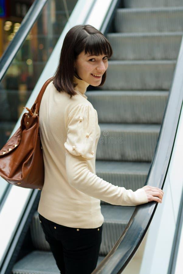 Une belle jeune femme sur l'escalator au centre commercial image stock