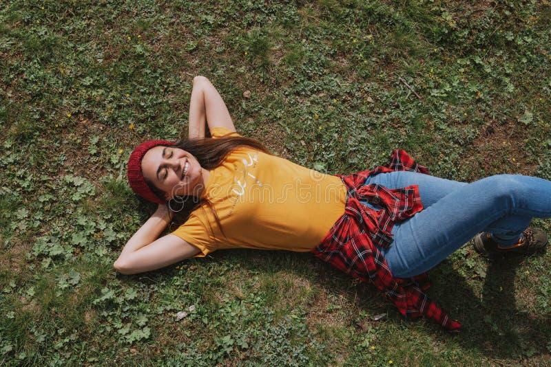 Une belle jeune femme se couche sur l'herbe, appréciant le ressort photographie stock libre de droits