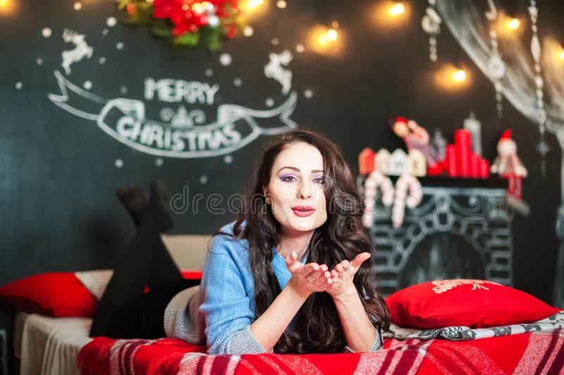 Une belle jeune femme sur le lit envoie un baiser d'air Brune dans la chambre à coucher décorée pour Noël photo stock
