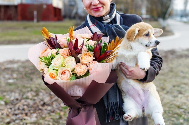 Une belle jeune femme tient un petit, mignon chien drôle et un beau bouquet des fleurs image stock