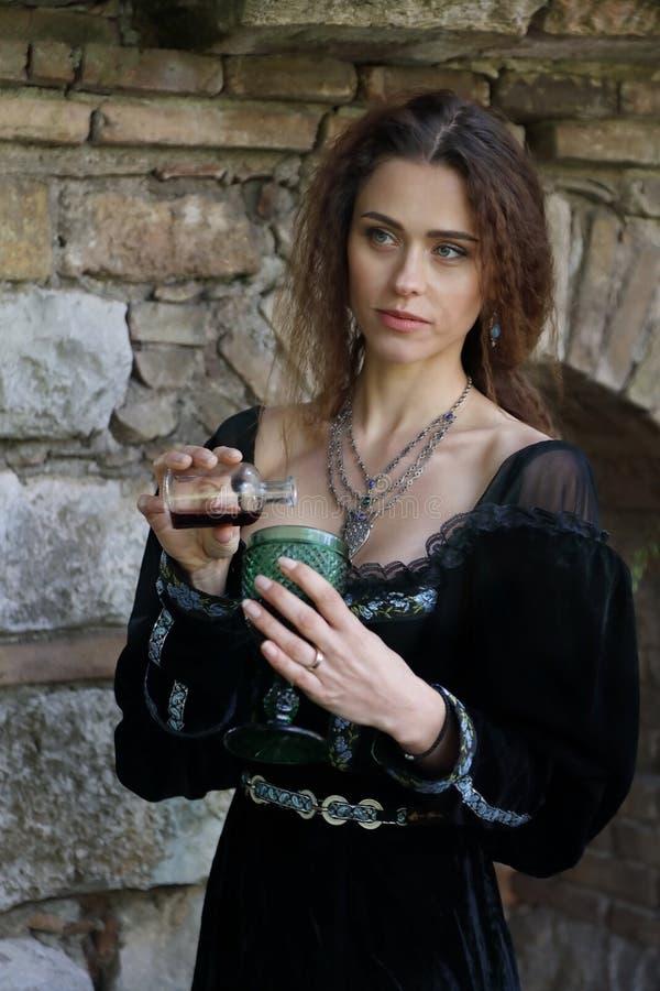 Une belle jeune femme verse un certain poison dans un verre image libre de droits