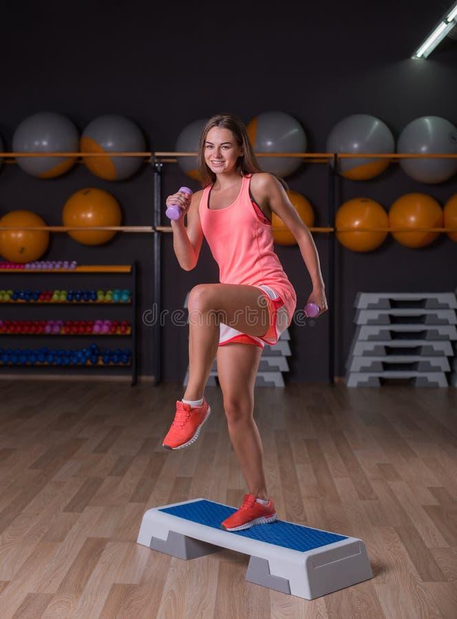 Une belle jeune fille avec des haltères s'exerçant sur un fond de gymnase Une fille folâtre dans les vêtements de sport colorés photos libres de droits