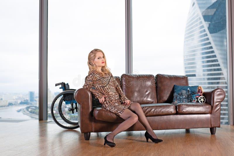 Une belle jeune fille blonde dans une robe à la mode avec une incapacité, posant sur un sofa en cuir sur le fond photographie stock libre de droits