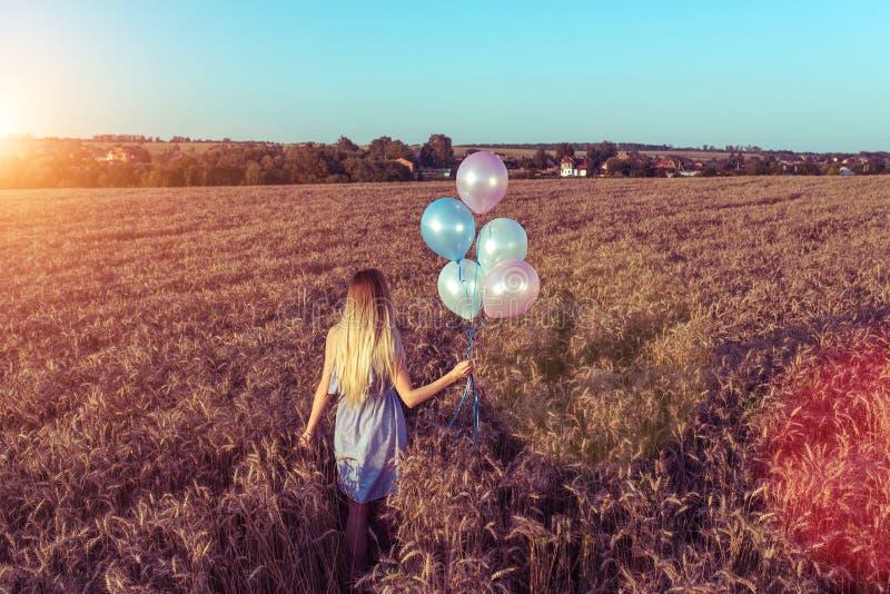 Une belle jeune fille bronzée en été dans la robe légère, un jour ensoleillé lumineux La main tient des ballons, laisse le blé photos libres de droits