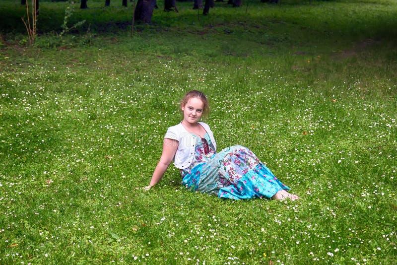 Une belle jeune fille dans une longue robe bleue s'assied sur l'herbe vert clair en parc images stock