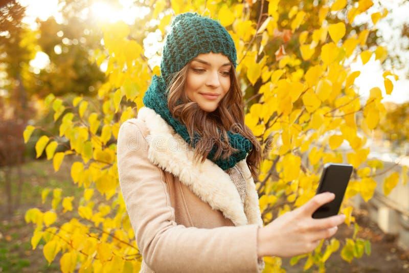 Une belle jeune fille marche par le parc d'automne sur le fond des feuilles brillamment colorées images stock