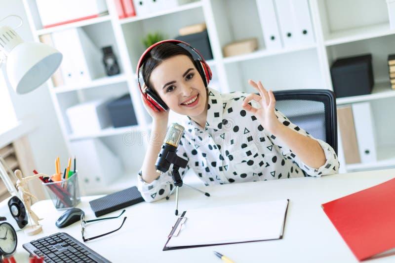 Une belle jeune fille s'assied dans des écouteurs et avec un microphone au bureau dans le bureau et montre un signe d'ok photo stock