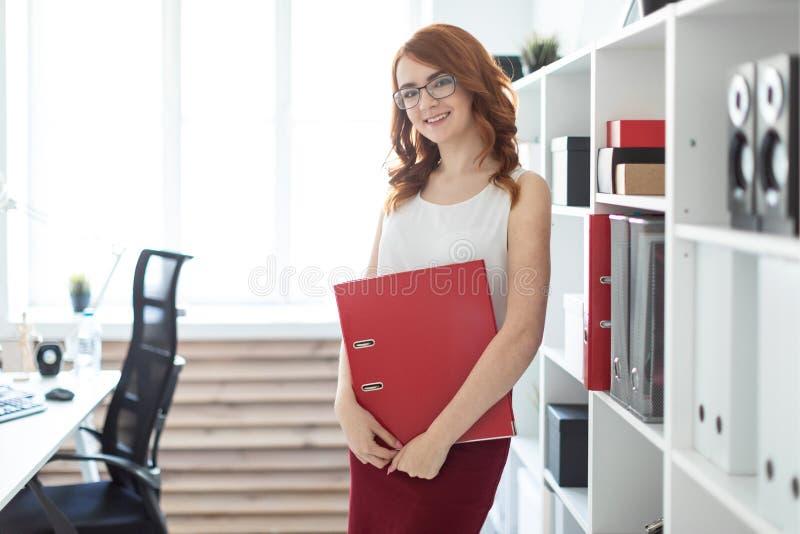 Une belle jeune fille se tient près d'une pile dans le bureau et tient un dossier avec des documents dans des ses mains photos libres de droits