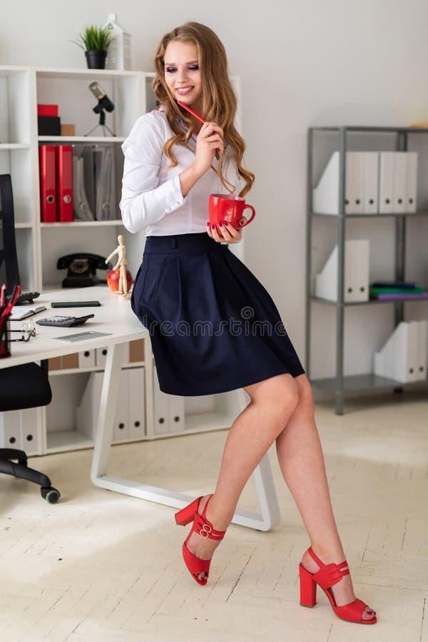 Une belle jeune fille se tient près d'une table dans le bureau et tient une tasse et un crayon rouges dans des ses mains images libres de droits