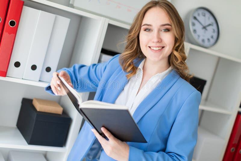 Une belle jeune fille se tient près d'un support dans le bureau et tient un livre ouvert dans des ses mains photo libre de droits