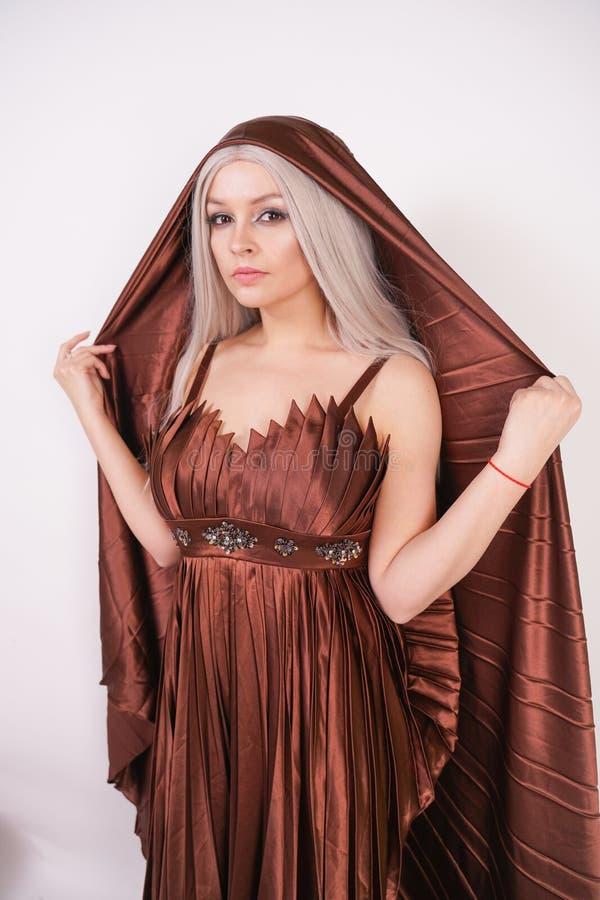 Une belle jeune fille tient dans une robe plissée par brun luxueux de soirée avec un couvert de tissu ses cheveux et tête sur le  photo libre de droits