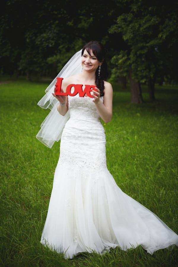 Une belle jeune mariée dans une robe blanche tient et tient les lettres en bois dans des ses mains photo libre de droits