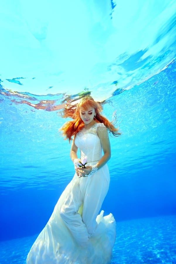 Une belle jeune mariée est nageante et posante sous l'eau dans la piscine dans une robe blanche un jour ensoleillé Elle tient la  photos libres de droits