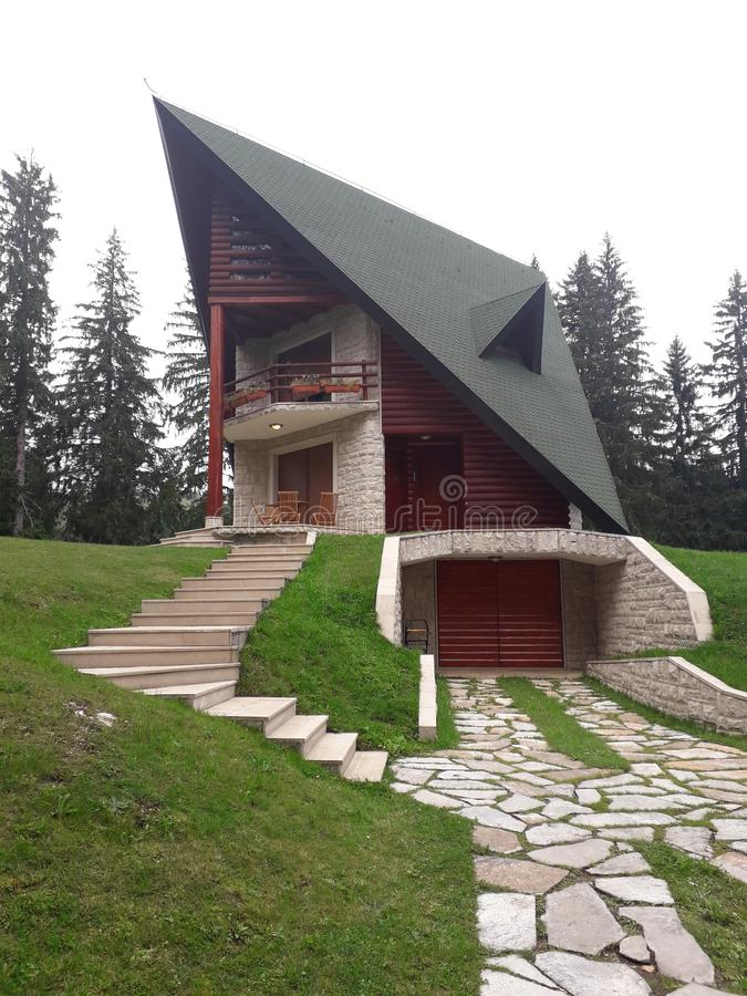 Une belle maison de montagne sur une colline est située dans la forêt à côté du lac image libre de droits