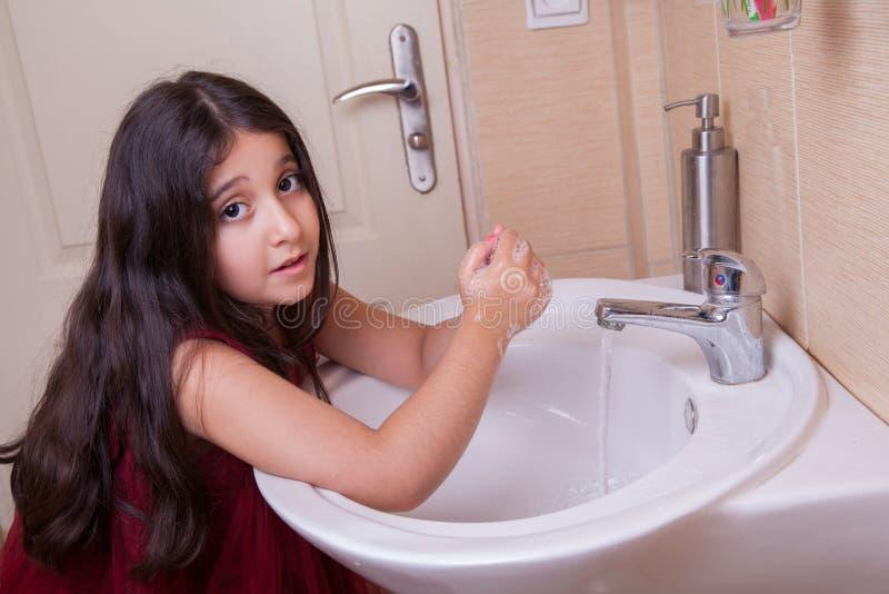 Une belle petite fille arabe du moyen orient avec la robe rouge se lave les mains dans la salle - Une belle salle de bain ...
