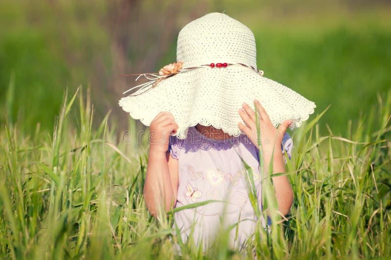 Une belle petite fille avec un chapeau dans un domaine de texture photo stock