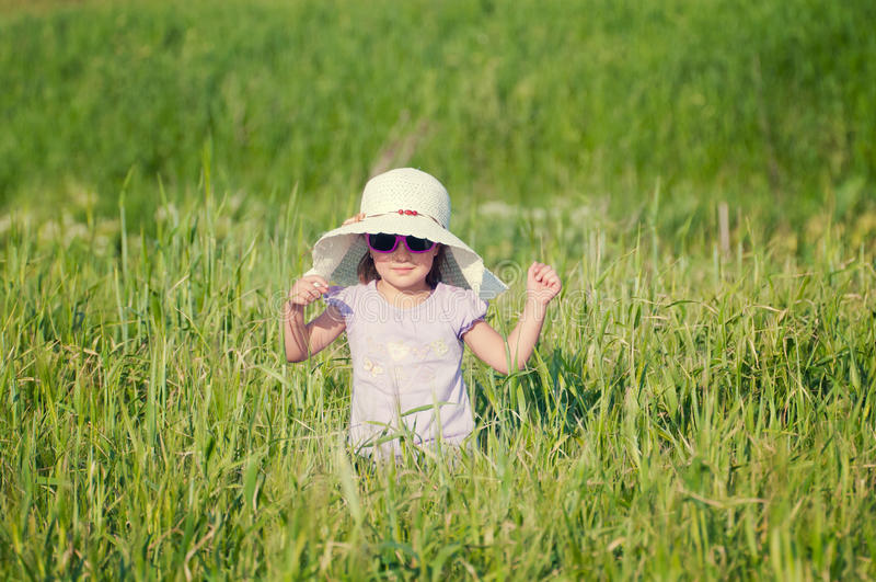 Une belle petite fille avec un chapeau dans un domaine de texture image libre de droits
