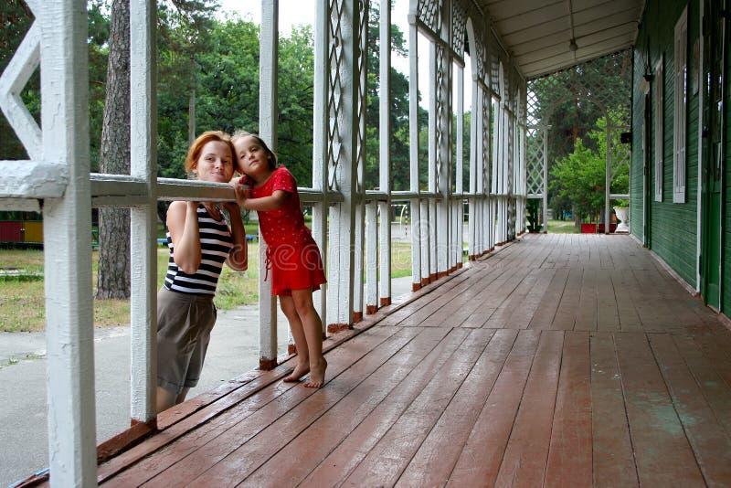 Une belle petite fille pliée à la jeune femme sur la terrasse de la maison de campagne en bois dehors photo stock