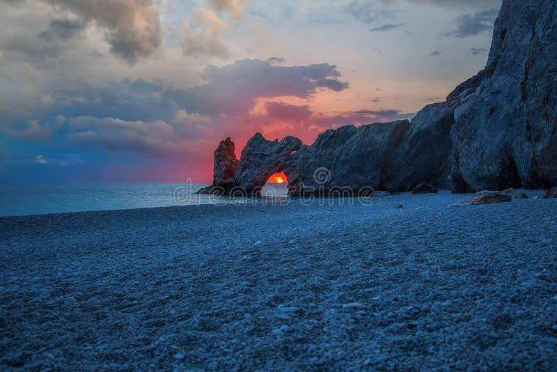 Une belle plage au lever de soleil avec le soleil dans le trou des roches image libre de droits