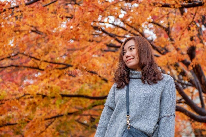 Une belle position asiatique de femme parmi l'arbre rouge et jaune de couleurs part en automne photographie stock