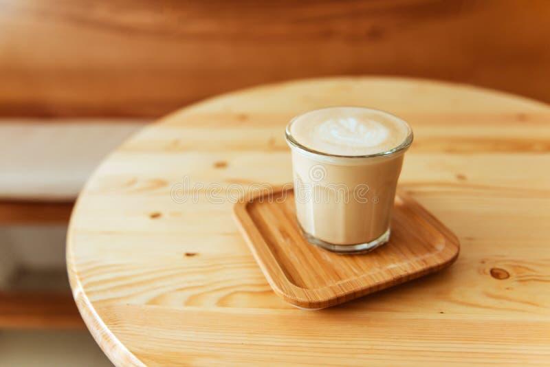 Une belle tasse de cappuccino avec l'art de latte à l'arrière-plan en bois de l'espace.  image stock