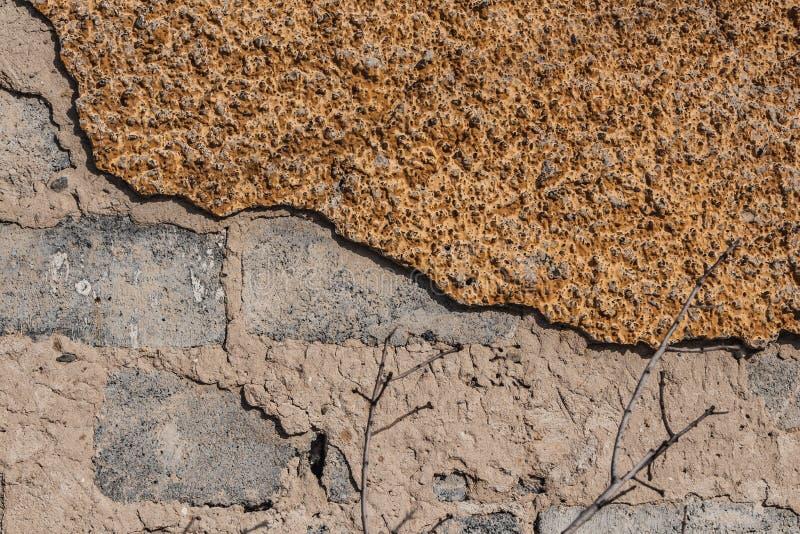 Une belle texture horizontale d'une partie d'un vieux mur de briques gris brisé avec le plâtre jaune sur la photo image libre de droits