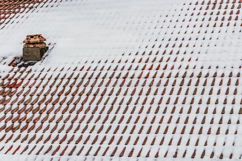 Une belle texture horizontale d'une partie d'un vieux toit brun humide des tuiles d'argile avec la neige blanche et une cheminée photo stock