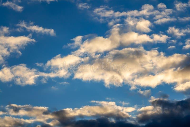 Une belle texture horizontale d'un ciel bleu avec les nuages blancs et oranges et gris lumineux photo stock