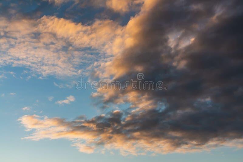 Une belle texture horizontale d'un ciel bleu avec les nuages blancs et oranges et gris lumineux image stock