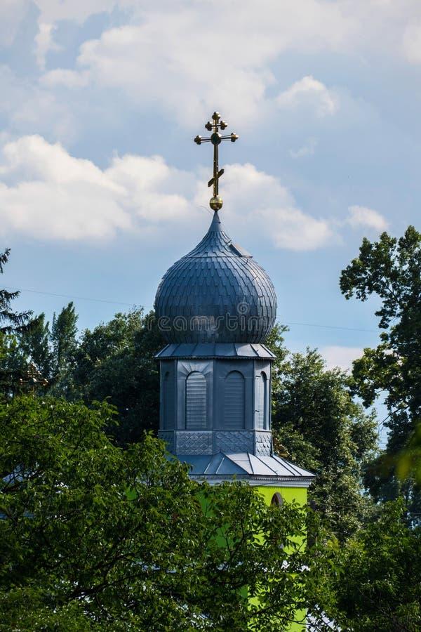 Une belle vue du dôme de scintillement de l'église avec une croix dorée se tenant parmi les arbres verts contre photographie stock