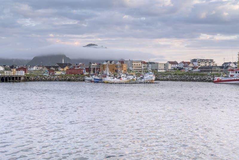 Une berge de brouillard peu profonde sur les bateaux de pêche au port du village à la tombée de la nuit, Andenes, Norvège image stock