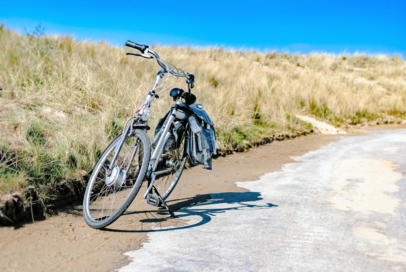 Une bicyclette garée le long d'une route côtière avec des dunes au fond Concept d'été Vacances Location de vélo biking tourisme image stock