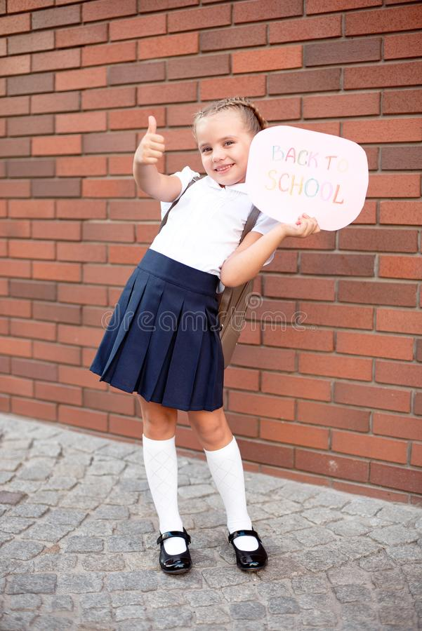 Une blonde de petite fille dans des supports d'uniforme scolaire près d'un mur de briques tenant un tableau noir avec le texte d images stock