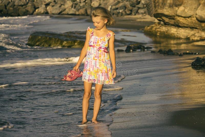 Une blonde rêveuse de fille dans une belle robe marche le long du rivage, foyer mou images libres de droits