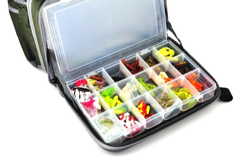Une boîte avec un grand choix de mensonges d'amorces de silicone dans un sac de pêche, fond blanc photos libres de droits