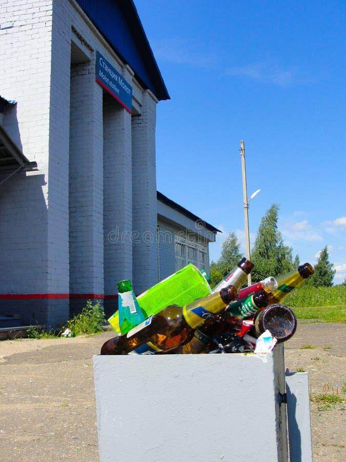 Une boîte de déchets débordant avec des bouteilles à bière est vue devant la gare, Russie photographie stock