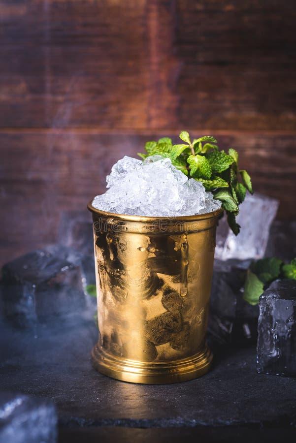 Une boîte en fer blanc avec de la glace est décorée d'un brin de menthe images libres de droits