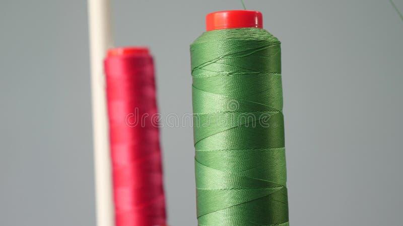 Une bobine de fil rouge et vert de coton sur l'axe de la machine ? coudre dans le premier plan, plan rapproch? Usine de couture images libres de droits