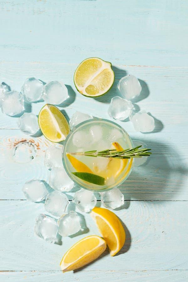 Une boisson régénératrice de chaux de citron avec des glaçons dans des gobelets en verre sur un fond bleu Cocktail d'?t? Copiez l photo stock