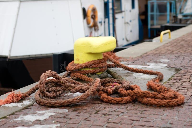 Une borne d'amarrage s'est enlacée avec une corde d'amarrage Bateaux amarrés à photos stock