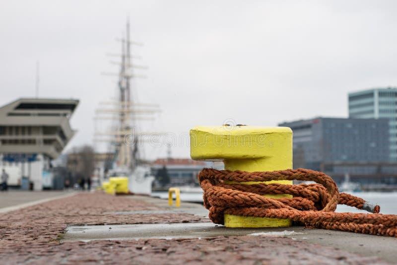 Une borne d'amarrage s'est enlacée avec une corde d'amarrage Bateaux amarrés à images stock