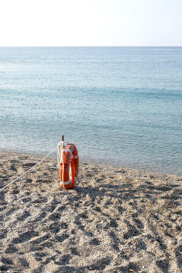 Une bouée de sauvetage sur une plage vide sur la côte italienne avec l'espace de copie pour votre texte photographie stock
