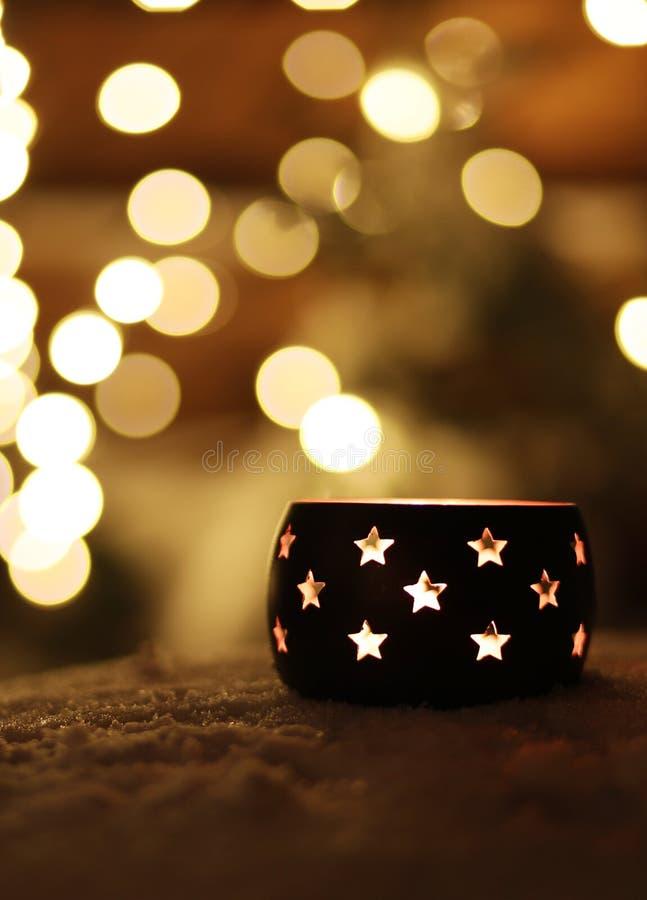 Une bougie avec des étoiles sur la neige pendant la nuit avec le fond de boche photographie stock libre de droits