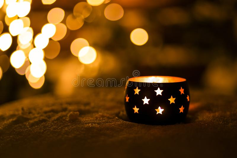 Une bougie avec des étoiles sur la neige pendant la nuit avec le fond de boche images libres de droits