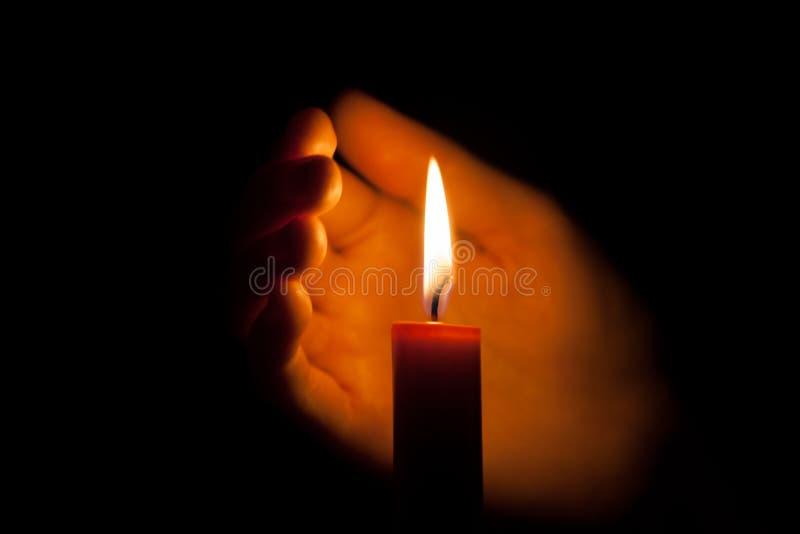 Une bougie brûlante la nuit, protégé par la main d'une femme Flamme de bougie rougeoyant sur un fond foncé avec l'espace libre po images stock