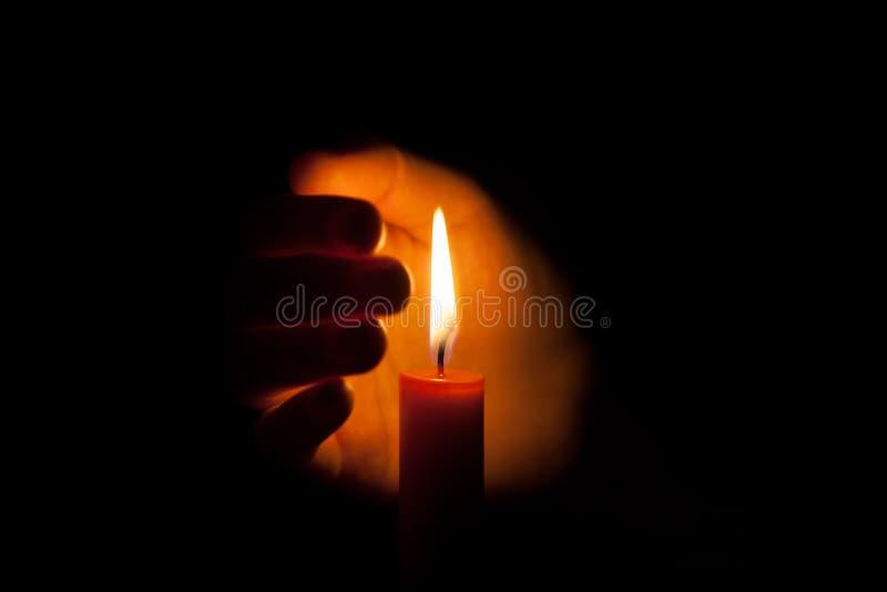 Une bougie brûlante la nuit, protégé par la main d'une femme Flamme de bougie rougeoyant sur un fond foncé avec l'espace libre po image libre de droits