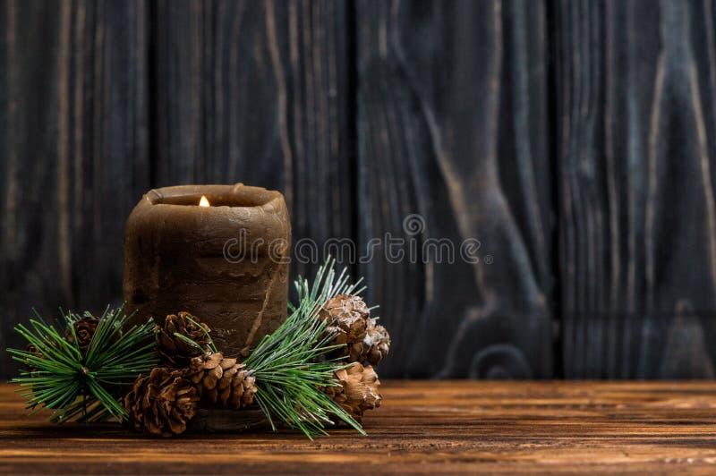 Une bougie brune allumée est décorée d'une branche impeccable avec de petits cônes photos libres de droits