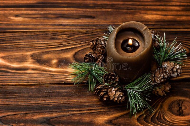 Une bougie brune allumée est décorée d'une branche impeccable Conseils en bois de Brown sur le fond photo stock